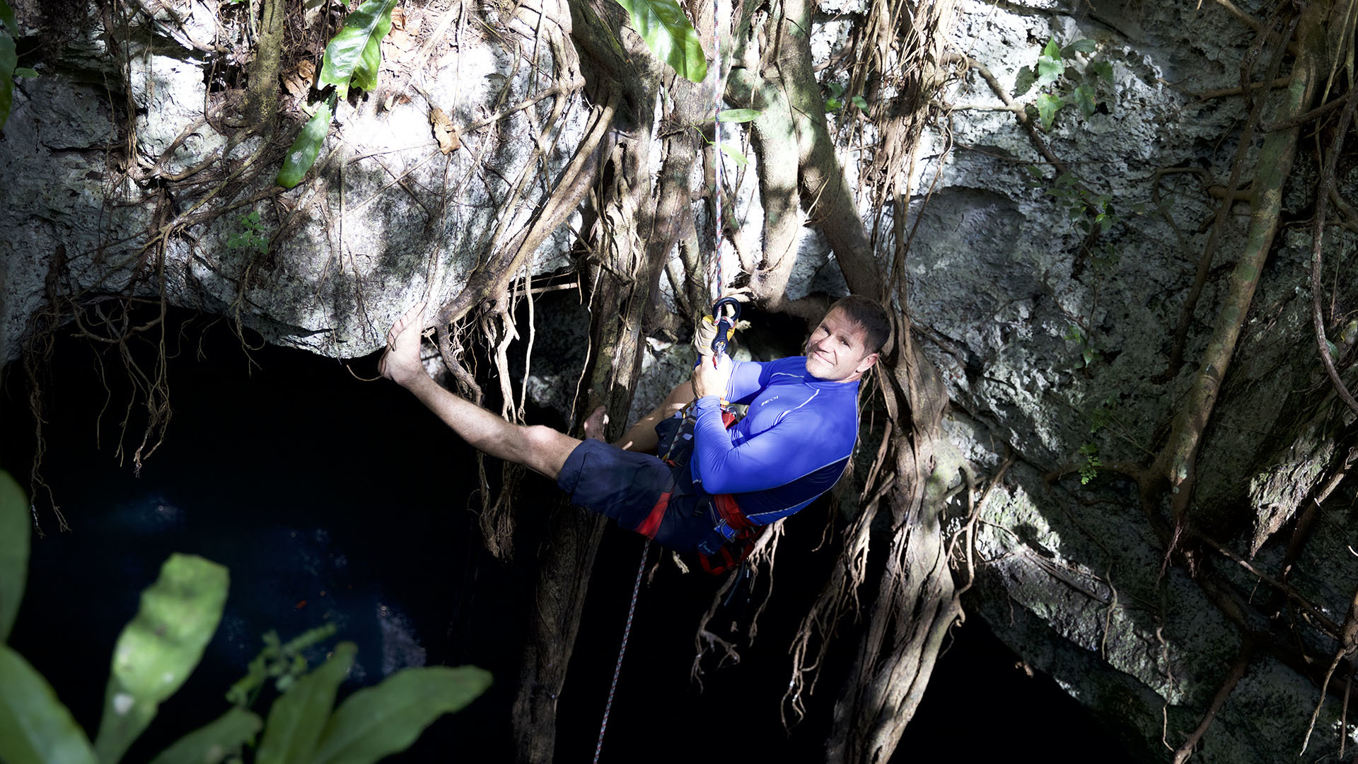 Image of Steve Backshall abseiling down a cenote.