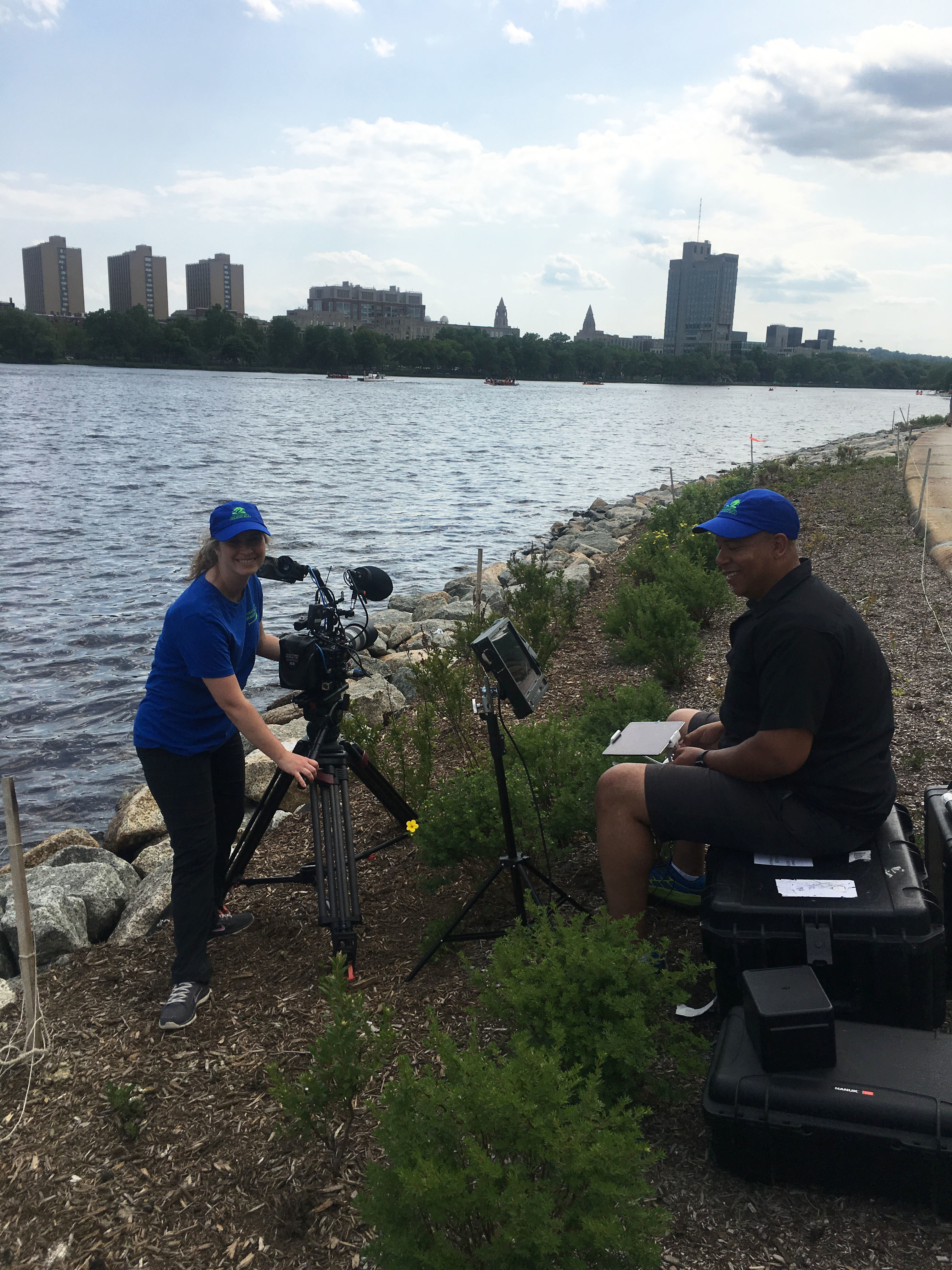 Filmmaker Katie Prentiss Onsager and Cinematographer Corey Lillard set up equipment on the bank of the Charles River.